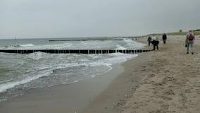 Povos que andam avante na praia de Graal-Muertz no tempo do outono clima de tempestade com ondas fortes tradicionalmente papagaio filme