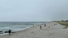 Povos que andam avante na praia de Graal Muertz no tempo do outono clima de tempestade com ondas fortes tradicionalmente papagaio filme