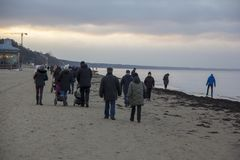 Povos que andam durante o por do sol em Sandy Beach do mar Báltico foto de stock royalty free
