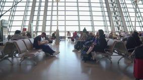 Povos que andam e que esperam no terminal do trânsito do aeroporto internacional Transporte aéreo, conceito do estilo de vida do  filme