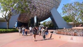 Povos que andam e que tomam imagens ao lado da esfera grande em Epcot na ?rea de Walt Disney World Resort vídeos de arquivo