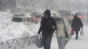 Povos que andam na cidade durante a queda de neve pesada, ciclone pacífico da neve filme