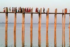 Povos que andam na ponte de madeira de U Bein no rio Ayeyarwad Fotos de Stock