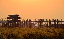 Povos que andam na ponte de madeira de U Bein no rio Ayeyarwad, Myanmar Fotografia de Stock