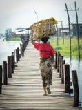 Povos que andam na ponte de madeira em Myanmar Imagens de Stock