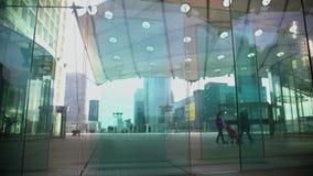 Povos que andam perto da entrada de vidro criativa no arranha-céus, arquitetura moderna filme