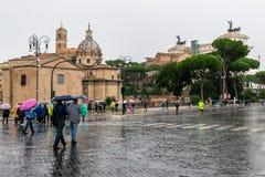 Povos que andam sobre atrav?s da rua de Dei Fori Imperiali O monumento de Vittorio Emanuele II altera-se da p?tria no fundo imagens de stock royalty free