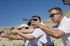 Povos que apontam armas da mão na escala de acendimento Imagem de Stock