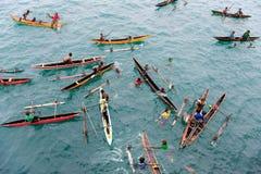 Povos que apreciam a chuva nas canoas no Oceano Pacífico imagem de stock