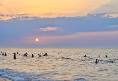 Povos que apreciam o mar e o por do sol! Imagem de Stock