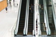 Povos que apressam-se na escada rolante Fotografia de Stock