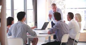 Povos que assistem à reunião de negócios no escritório de plano aberto moderno