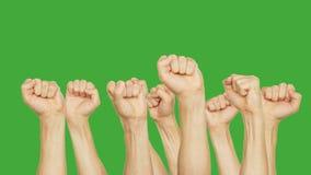 Povos que aumentam o punho acima apertado na reunião na multidão no fundo verde Aglomere-se movendo os punhos da mão na chave ver vídeos de arquivo