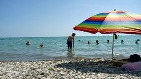 Povos que banham-se no sol, natação e jogando jogos na praia E Foto de Stock
