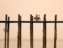 Povos que biking na ponte de madeira em Mandalay, Myanmar Fotografia de Stock