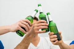 Povos que brindam garrafas de cerveja Fotos de Stock Royalty Free