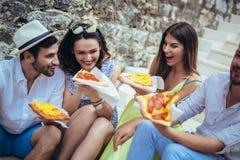 Povos que comem o fast food na cidade ao viajar imagem de stock