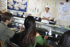 Povos que comem o sushi no restaurante japonês Fotos de Stock Royalty Free