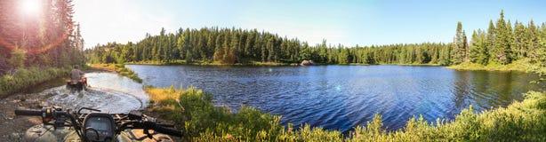 Povos que conduzem quadriláteros de ATV através da água Lago em Ontário, Canadá Fotografia de Stock
