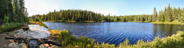 Povos que conduzem quadriláteros de ATV através da água Lago em Ontário, Canadá Foto de Stock
