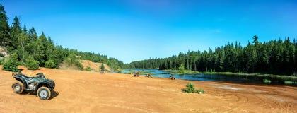 Povos que conduzem quadriláteros de ATV na praia da areia no lago Fotos de Stock