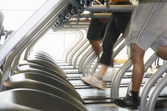 Povos que correm em escadas rolantes no health club Imagens de Stock