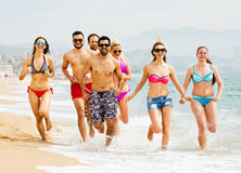 Povos que correm na praia Imagem de Stock Royalty Free
