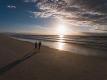 Povos que correm na praia na manhã Fotografia de Stock