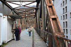 Povos que cruzam o cruzamento resistido jugoslavo velho da ponte do metal em Bósnia Hercegovina Foto de Stock