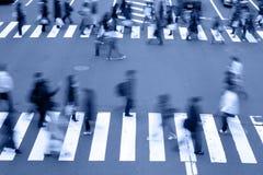 Povos que cruzam os tons rua-azuis Fotos de Stock Royalty Free