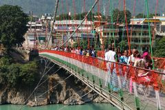 Povos que cruzam a ponte de Laxman Jhula Rishikesh, India fotografia de stock