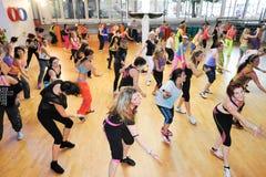Povos que dançam durante a aptidão do treinamento de Zumba em um gym