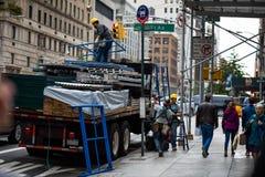 Povos que descarregam o caminhão com os andaimes na 5a avenida, New York Foto de Stock