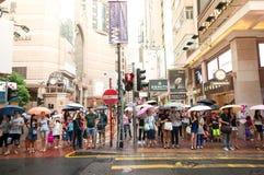 Povos que esperam à cruz através das ruas movimentadas em Hong Kong Times Foto de Stock