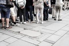 Povos que esperam na linha para entrar para baixo na construção da cintura Foto de Stock Royalty Free