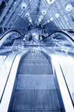 Povos que estão na escada rolante no centro de negócios Imagens de Stock
