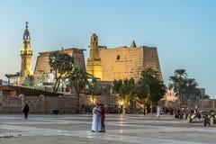 Povos que estão no quadrado com seus telefones celulares na frente do Templo de Luxor iluminado na noite com céu azul e incandesc imagens de stock royalty free