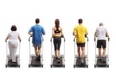 Povos que exercitam em escadas rolantes Foto de Stock Royalty Free