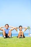 Povos que exercitam - fazer dos pares senta-se levanta fora Imagem de Stock Royalty Free