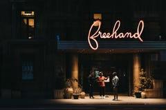 Povos que falam sob o sinal iluminado do hotel a mão livre em F fotografia de stock royalty free