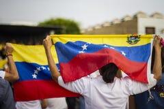 Povos que guardam o protesto venezuelano da bandeira foto de stock