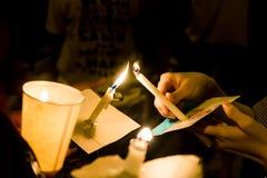 Povos que iluminam a vigília da vela na esperança procurando da escuridão, adoração, Imagens de Stock