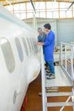 Povos que inspecionam a fuselagem de aviões fotografia de stock royalty free