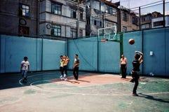 Povos que jogam o basquetebol no campo aberto da rua em uma área residencial imagem de stock royalty free