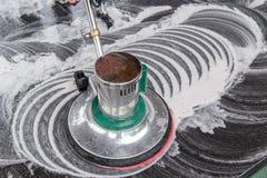Povos que limpam o assoalho preto do granito com a máquina e químico tailandeses Foto de Stock