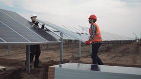 Povos que montam os painéis solares Fotografia de Stock Royalty Free