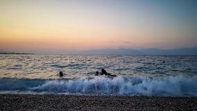 povos que nadam na praia do por do sol imagens de stock