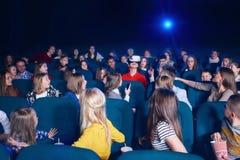 Povos que olham o menino que veste vidros virtuais no teatro de filme Fotos de Stock