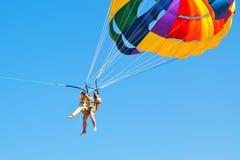 Povos que parakiting no paraquedas no céu azul Fotografia de Stock