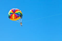 Povos que parascending no paraquedas no céu azul Fotografia de Stock